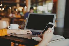 Jonge bedrijfs vrouwelijke handen die smartphone gebruiken terwijl het werken aan computer stock foto