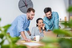 Jonge bedrijfscollega's die met laptop in bureau samenwerken Stock Afbeelding