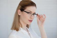 Jonge bedrijfsdame in witte overhemd en glazen Het aantrekkelijke jonge vrouw glimlachen royalty-vrije stock foto's