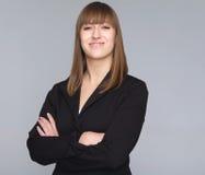 Jonge bedrijfsdievrouw op grijze achtergrond wordt geïsoleerd Stock Foto's