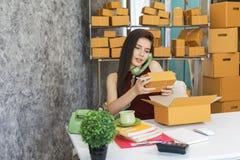Jonge bedrijfseigenaar die als online freelancer de doos en c controleren stock afbeelding