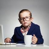 Jonge bedrijfsjongen kind in glazen weinig werkgever in bureau Stock Afbeelding
