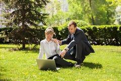 Jonge bedrijfsman en vrouw die laptop in park met behulp van Royalty-vrije Stock Foto