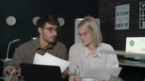 Jonge bedrijfsman en vrouw die voorlaptop in donker bureau samenwerken stock video