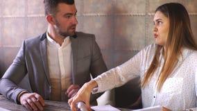 Jonge bedrijfsman en vrouwenzitting in koffie en het bespreken van contract stock videobeelden