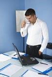 Jonge bedrijfsmens in bureau Stock Afbeelding