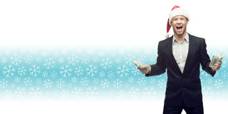 Jonge bedrijfsmens in de holdingsgeld van de santahoed over de winter backgr Royalty-vrije Stock Afbeelding