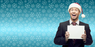 Jonge bedrijfsmens in de holdingsteken van de santahoed over de winterbackgro Stock Fotografie