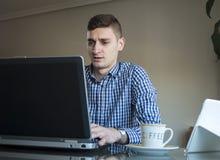 Jonge bedrijfsmens die aan zijn laptop thuis bureau werkt Royalty-vrije Stock Fotografie