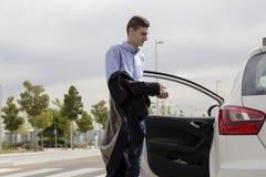 Jonge bedrijfsmens die binnen witte auto krijgen Stock Afbeelding