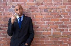 Jonge bedrijfsmens die en het drinken wijn denkt stock fotografie