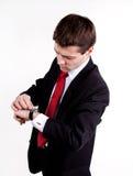 Jonge bedrijfsmens die op zijn horloge kijkt Stock Foto