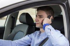 Jonge bedrijfsmens die op zijn telefoon binnen auto spreken Royalty-vrije Stock Afbeeldingen