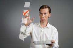 Jonge bedrijfsmens die in wit overhemd met tabletcomputer op controlelijstdoos controleren Grijze achtergrond Royalty-vrije Stock Foto