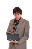 Jonge bedrijfsmens die zich met laptop bevindt Royalty-vrije Stock Foto's