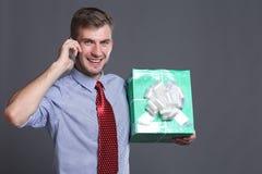 Jonge bedrijfsmens met giften stock foto