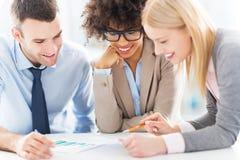 Jonge bedrijfsmensen die in bureau bespreken