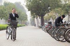 Jonge bedrijfsmensen die hun fietsen parkeren en op de telefoon op de stoep in Peking, China spreken Royalty-vrije Stock Foto's