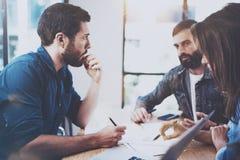 Jonge bedrijfsmensen die nieuw project in modern bureau bespreken Triomedewerkers die gesprekken maken op vergadering stock foto