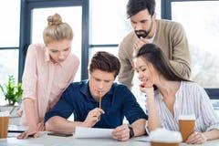 Jonge bedrijfsmensen die nieuw project op kleine commerciële vergadering bespreken stock foto's