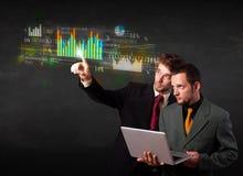 Jonge bedrijfsmensen wat betreft kleurrijke grafieken en diagrammen Stock Foto's