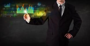 Jonge bedrijfspersoon wat betreft kleurrijke grafieken en diagrammen Stock Afbeeldingen