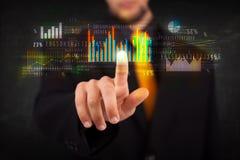 Jonge bedrijfspersoon wat betreft kleurrijke grafieken en diagrammen Royalty-vrije Stock Afbeelding