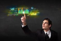 Jonge bedrijfspersoon wat betreft kleurrijke grafieken en diagrammen Stock Fotografie