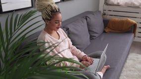 Jonge bedrijfsvrouw die aan camera bekijken en laptop werken die thuis glimlachen stock footage