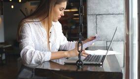 Jonge bedrijfsvrouw die aan een laptop holdingsdocumenten werken in handen stock footage