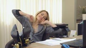 Jonge bedrijfsvrouw die bij een modern bureau voor laptop geeuwen stock videobeelden