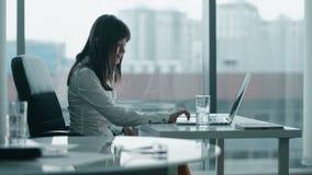 Jonge bedrijfsvrouw die bij laptop in modern bureau werken stock videobeelden
