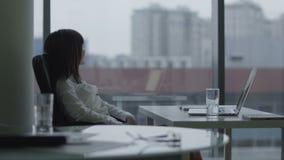 Jonge bedrijfsvrouw die bij laptop in modern bureau werken zij die en neemt een onderbreking glimlachen stock video