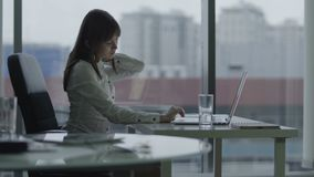 Jonge bedrijfsvrouw die bij laptop in modern bureau werken zij houdt op omdat achter kwetst is stock videobeelden