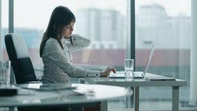 Jonge bedrijfsvrouw die bij laptop in modern bureau werken zij houdt op omdat achter kwetst is stock video