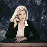 Jonge bedrijfsvrouw die celtelefoon in stadspark uitnodigen royalty-vrije stock fotografie