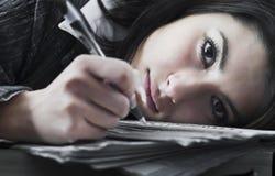 Jonge bedrijfsvrouw die door haar baan wordt overweldigd Stock Foto's