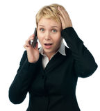 Jonge bedrijfsvrouw die door telefoonbespreking wordt geschokt Stock Fotografie