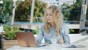 Jonge bedrijfsvrouw die in een koffie aan de de zomergrond werken Hij eet roomijs, gebruikt laptop stock video