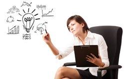 Jonge bedrijfsvrouw die gloeilamp met diverse diagrammen trekken Stock Foto