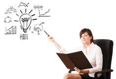 Jonge bedrijfsvrouw die gloeilamp met diverse diagrammen voorstellen Royalty-vrije Stock Foto