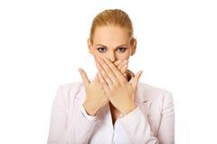 Jonge bedrijfsvrouw die haar mond behandelen met twee handen royalty-vrije stock afbeelding