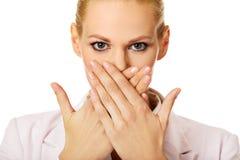 Jonge bedrijfsvrouw die haar mond behandelen met twee handen stock fotografie
