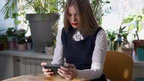 Jonge bedrijfsvrouw die haar smartphone in koffie met heel wat groene installaties gebruiken stock videobeelden
