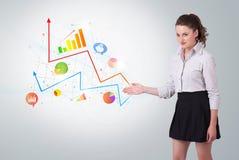 Jonge bedrijfsvrouw die kleurrijke grafieken voorlegt royalty-vrije stock foto's