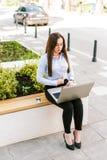 Jonge Bedrijfsvrouw die Laptop met behulp van terwijl Openlucht Zitten royalty-vrije stock foto
