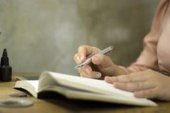 Jonge bedrijfsvrouw die met een pen op kantoor werken, zij die overwerk blijven royalty-vrije stock fotografie