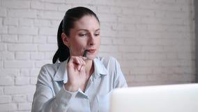 Jonge bedrijfsvrouw die met laptop werken en over toekomst op open plekkantoor denken in modern binnenland stock footage