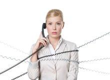 Jonge bedrijfsvrouw die met telefoonkoord wordt gebonden Stock Fotografie