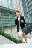 Jonge bedrijfsvrouw die omhoog de stap en het praatje op mobiele phon lopen royalty-vrije stock fotografie